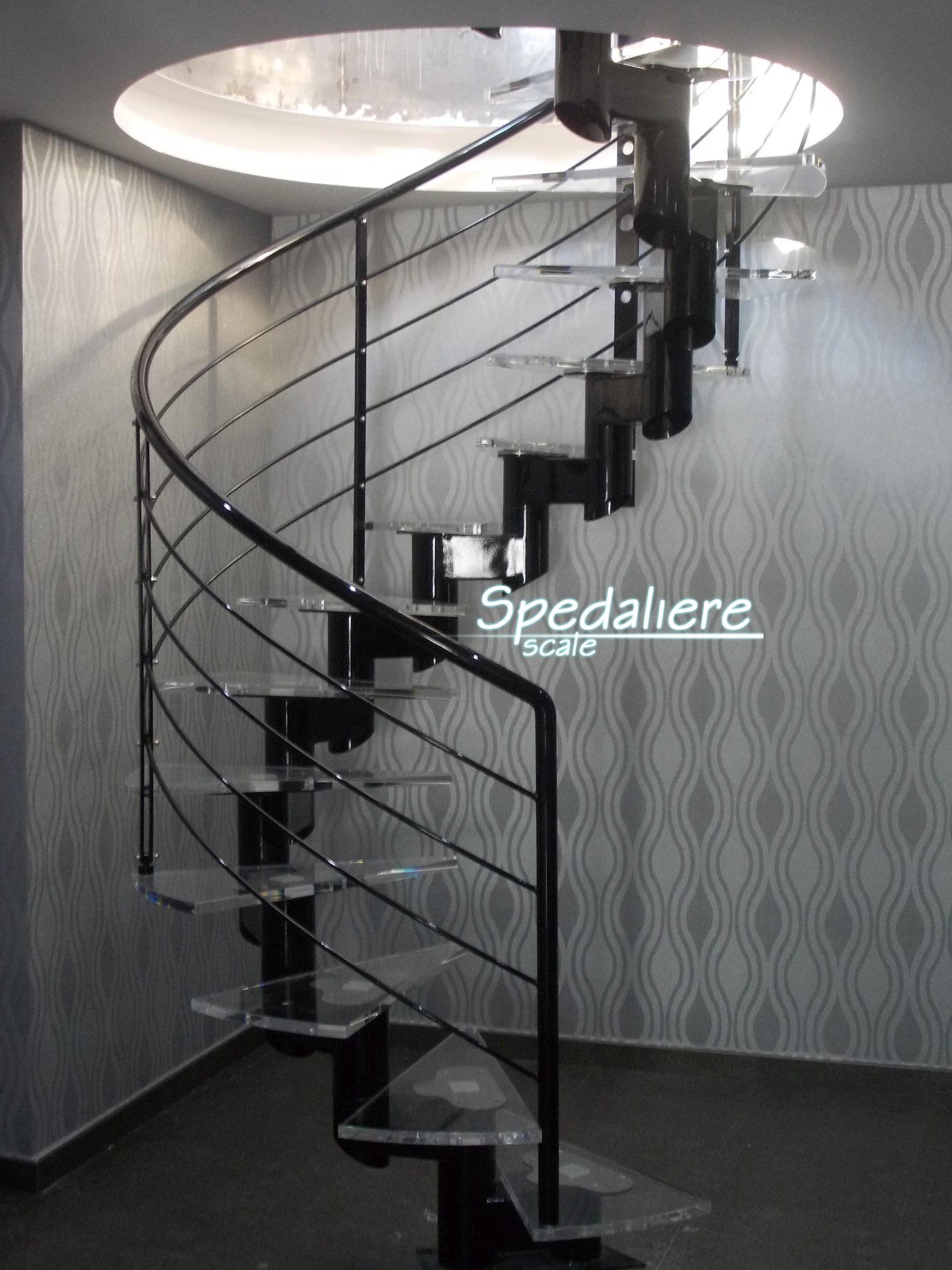 Elicoidale mono trave realizzata con gradini in plexiglas trasparente finiture nero lucido, illuminata