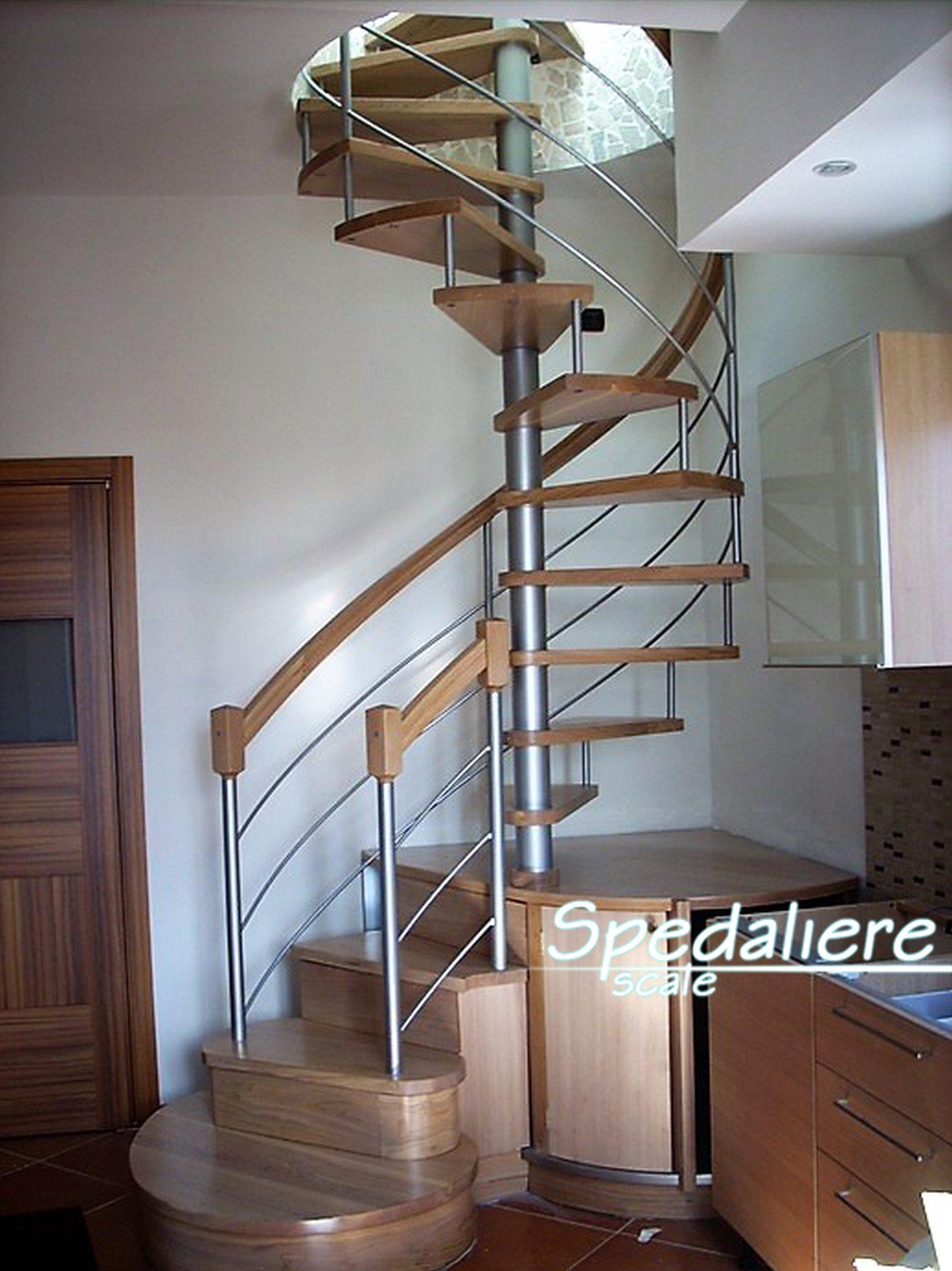 Scala a chiocciola con primi gradini curvi interamente in legno massello con integrazione del mobile ad ante curve